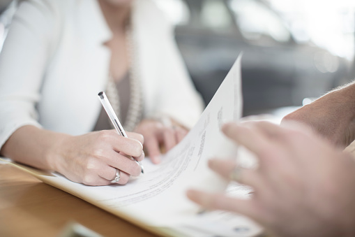 Woman signing contract at desk at car dealership
